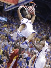 Kansas guard Travis Releford delivers a dunk over Pittsburg State guard Marky Nolen and teammate Justin Wesley during the second half on Tuesday, Nov. 1, 2011 at Allen Fieldhouse.