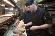 Sous chef Nicholas Haxton, right, plates up his cooked turkey piccata he prepared in the kitchen at The Eldridge, 701 Mass.  He works alongside new executive chef Todd Schneekloth. Turkey piccata is an alternative way to prepare those deeply discounted turkeys that seem to be easy to find this time of year.