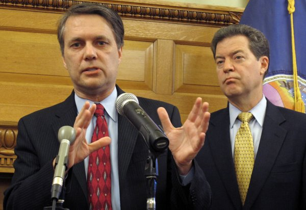 Kansas Lt. Gov. Jeff Colyer, left, discusses proposed changes for the state&#39;s Medicaid program, Tuesday, Nov. 8, 2011, at the Statehouse in Topeka. Watching to his right is Gov. Sam Brownback, who had Colyer lead the team drafting the proposals.