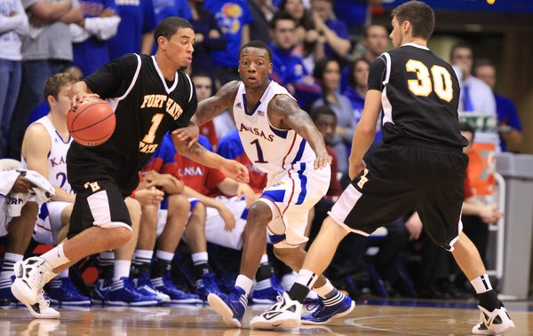 Kansas guard Naadir Tharpe looks to fight through a screen by Fort Hays State forward K.C. Rodenburg (30) while defending Omar McDade (1) during the first half on Tuesday, Nov. 8, 2011 at Allen Fieldhouse.