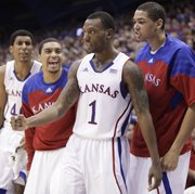 Kansas guard Naadir Tharpe pumps his fist after converting a bucket after being fouled by a Fort Hays State defender during the second half on Tuesday, Nov. 8, 2011 at Allen Fieldhouse. Pictured are teammates Kevin Young, left, Niko Roberts and Merv Lindsay.