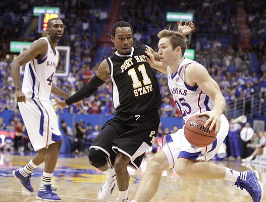 Kansas guard Jordan Juenemann drives against Fort Hays State guard Tyrone Phillips during the second half on Tuesday, Nov. 8, 2011 at Allen Fieldhouse. At right is Kansas forward Justin Wesley.