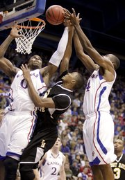 Kansas forwards Thomas Robinson, left, and Justin Wesley get up for a rebound over Fort Hays State guard Lance Russell during the first half on Tuesday, Nov. 8, 2011 at Allen Fieldhouse.