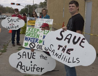 Demonstrators against the proposed Keystone XL pipeline, protest outside the law offices of Nebraska Speaker of the Legislature Mike Flood, in Norfolk, Neb., Tuesday, Oct. 11, 2011, while Alex Pourbaix, president of TransCanada Corp.'s energy and oil pipelines, holds a meeting inside with state senators to discuss the proposed route of the Keystone XL pipeline through the state.