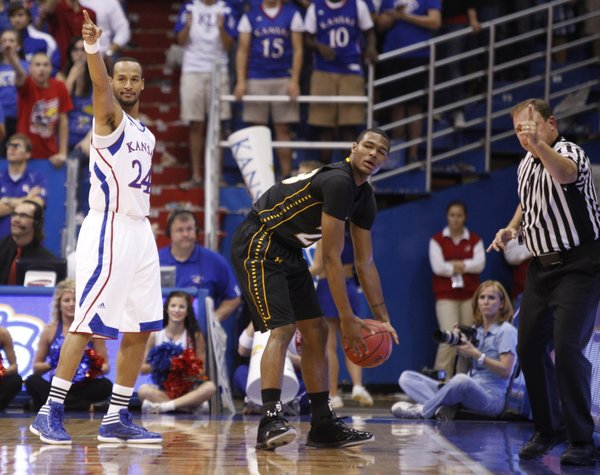 Kansas guard Travis Releford signals the ball going the Jayhawks way along with a game official after forcing it out of bounds off Towson forward Deon Jones during the first half on Friday, Nov. 11, 2011 at Allen Fieldhouse.