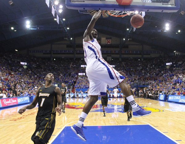 Kansas guard Tyshawn Taylor throws down a dunk off a breakaway before Towson forward Marcus Damas during the second half on Friday, Nov. 11, 2011 at Allen Fieldhouse.