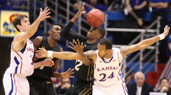 Kansas players Conner Teahan, left, and Travis Releford tangle with Towson players Marcus Damas, left, and Enrique Gumbs as the teams vie for a loose ball during the second half on Friday, Nov. 11, 2011 at Allen Fieldhouse.