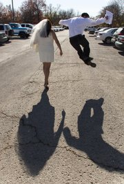Joel Carbough, right, jumps in the air in an attempt to click his heels after he and Felicia Hernandez got married Friday, Nov. 11, 2011, at the Douglas County Judicial and Law Enforcement Center at 111 E. 11th St.