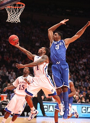 Kansas guard Naadir Tharpe extends to the bucket as Kentucky forward Terrance Jones swoops in to swat his shot during the first half on Tuesday, Nov. 15, 2011 at Madison Square Garden in New York.