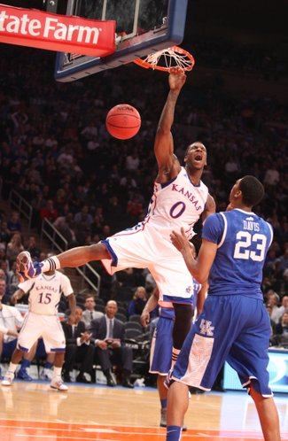 Kansas forward Thomas Robinson hangs on the rim after a dunk over Kentucky forward Anthony Davis during the first half on Tuesday, Nov. 15, 2011 at Madison Square Garden in New York.