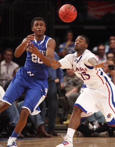 Kansas guard Elijah Johnson and Kentucky guard Doron Lamb collide while going for a loose ball during the second half on Tuesday, Nov. 15, 2011 at Madison Square Garden in New York.
