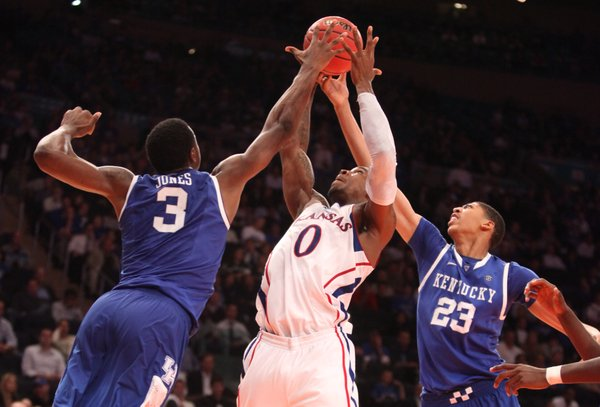 Kansas forward Thomas Robinson is hounded by Kentucky defenders Terrence Jones (3) and Anthony Davis (23) while going for a rebound during the second half on Tuesday, Nov. 15, 2011 at Madison Square Garden in New York.