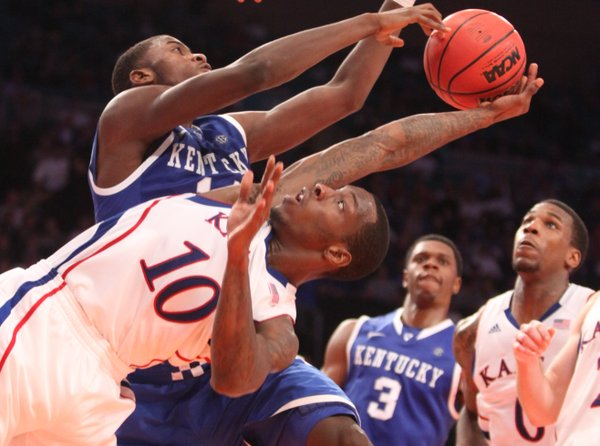 Kansas guard Tyshawn Taylor is smothered by Kentucky forward Michael Kidd-Gilchrist during the second half on Tuesday, Nov. 15, 2011 at Madison Square Garden in New York.