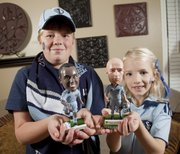 Ben Urban, 10, and his sister Grace, 8, along with their parents, are big fans of Sporting KC soccer team. The two hold bobble-head dolls of two of their favorite KC players.