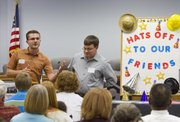 Andrew Nussbaum, left, had a few words to celebrate his brother Jesse, right, and his work at Free State High. A Friends of Education reception was help Wednesday at the Lawrence school district offices as part of an American Education Week celebration of school volunteerism.