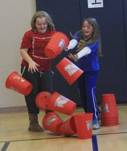 Ellie Robertson and Katie Spencer watch their stack of cups crash to the ground as physical education students at Lecompton Elementary School try to set a world record in cup stacking on Thursday, Nov. 17, 2011.