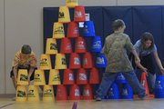 Josh Kibbee, Jordan Martin and Talen Malloy stack jumbo cups on a large scale. The three are part of a physical education class at Lecompton Elementary School, which tried to set a world record in cup stacking on Thursday, Nov. 17, 2011.