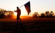 A Buddhist monk carries American and Kansas flags at daybreak Friday, Oct. 28, 2011, in Saline County south of Salina, Kansas. The flags were placed at the road entrance to The Buddhist Temple of Kansas.