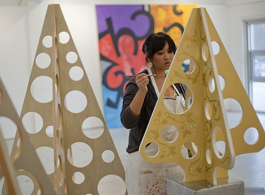 Winona Boado, 18, an apprentice artist at Van Go Mobile Arts Inc., paints some handmade wooden trees on Monday that will be in the annual Adornment Holiday Sale, Show and Party Saturday at 715 N.J. The sale, from 7 p.m. to 10 p.m., will feature items made by the young artists who have been receiving job training at Van Go.