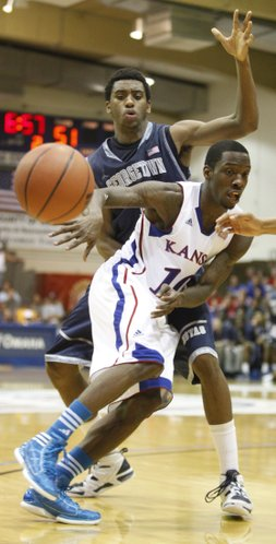 Kansas guard Tyshawn Taylor dishes a pass around Georgetown forward Hollis Thompson during the second half on Monday, Nov. 21, 2011 at the Lahaina Civic Center.