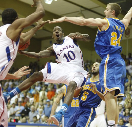 Kansas guard Tyshawn Taylor hangs in the air for a bucket as he is defended by UCLA forward Travis Wear (24) and Jerime Anderson (5) during the second half Tuesday, Nov. 22, 2011 at the Lahaina Civic Center.