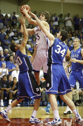 Kansas center Jeff Withey is fouled on the way up between Duke defenders Seth Curry and Ryan Kelly during the first half Wednesday, Nov. 23, 2011 at the Lahaina Civic Center.