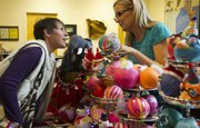 Kim Lybarger, left, Lawrence, leans in to listen while Barbara Burket explains treasure balls during Bizarre Bazaar on Saturday at the Lawrence Arts Center, 940 N.H. Treasure balls, a German tradition that Burket grew up with, are crepe paper balls meant to be unwrapped to reveal presents contained inside. Burket said she tries to make her treasure balls too pretty to unwrap.