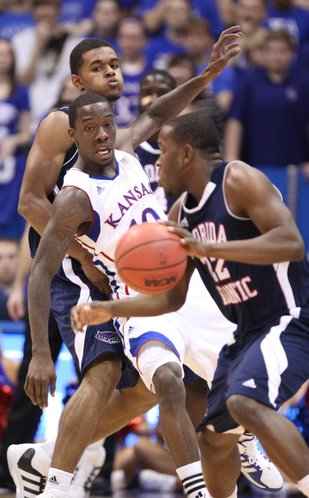 Kansas guard Tyshawn Taylor fights through a screen as he defends Florida Atlantic guard Greg Gantt during the first half Wednesday, Nov. 30, 2011 at Allen Fieldhouse.