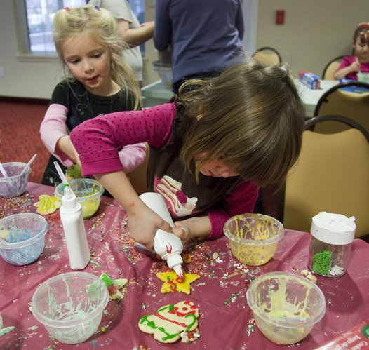 Taylor McCarthy, 4, left, and Estelle Bass, 4, work on the cookie line with residents at Meadowlark Estates to decorate Christmas cookies that will be sold as a fundraiser for the Lawrence Arts Center Preschool.