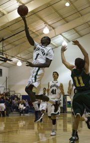 Seabury's Khadre Lane (1) glides past Olpe's Toby Smith (11) on his way to the hoop Friday, Dec. 2, 2011 in Lawrence.