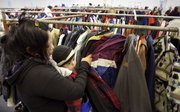 Maria Jamica, of Lawrence, searches for a coat with her 8-month-old son, Joel, shortly after the opening of the 25th annual Scotch Share the Warmth Coat Giveaway Friday at the I-70 Business Center.