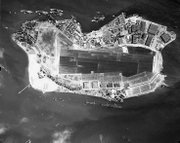 """Ford Island at Pearl Harbor, Nov. 1941. """"Battleship Row"""" is seen at the top of the image."""