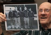 In this Dec. 1, 2011 photo, Maj. Thomas Griffin holds a photo at his home in Cincinnati, showing the flight crew of the U.S. Army Air Force B-25B Mitchell bomber on which he was a navigator for Doolittle's raid on Japan in 1942. Griffin, who was a lieutenant at the time, is pictured at left, along with, left to right, pilot Lt. Harold Watson, T/Sgt. Eldred Scott, Lt. James Parker, and Sgt. Wayne Bissell. (AP Photo/Al Behrman)
