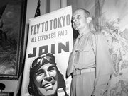 In this May 19, 1942 file photo, U.S. Army Air Corps Brig. Gen. Jimmy Doolittle poses with a new Air Corps poster in Washington. A month before, on April 18, Doolittle led 16 North American B-25s from the flight deck of the USS Hornet for the Army's first air raid on Tokyo. Coming just four months after the Imperial Japanese Navy savaged the U.S. Pacific Fleet at Pearl Harbor, the Doolittle raid on Japan's home did little damage, but lifted the spirits of Americans and electrified a world at war. (AP Photo, File)