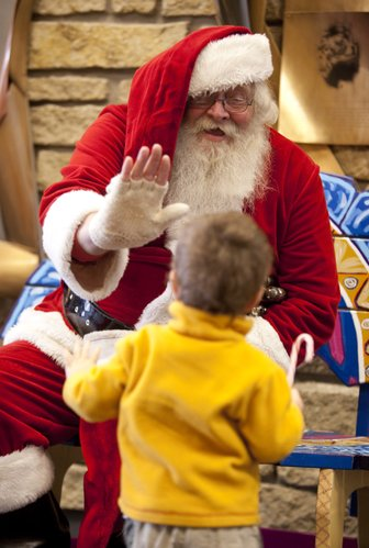 Lawrence Santa, Bob Beebe, 60, looks for a high five from Gage Kemme, 2, on Friday, Dec. 2, 2011 at the Lawrence Public Library. Beebe is disabled and recovering from a head injury suffered years ago. This year, Beebe hopes to raise enough money to cover the cost of a VanGo Mobile Arts bench for the Schiefelbusch Clinic at Kansas University, where Beebe received help in recovering his ability to communicate after his injury.