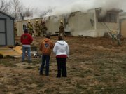 Smoke pours out of a home at the Brookwood Mobile Home Park, 1908 E. 19th St., on Monday, Dec. 5, 2011.