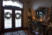 Wreaths and holiday table decorations add warmth just inside the front entrance of the home of Trish Van Vilet.