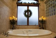 Simple decoration of greenery in the master bath helps carry the Christmas look throughout the home of Trish Van Vliet.