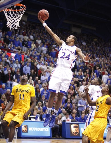 Kansas guard Travis Releford elevates to the bucket between Long Beach State defenders James Ennis (11) Casper Ware (22) and teammate Elijah Johnson during the first half Tuesday, Dec. 6, 2011 at Allen Fieldhouse.