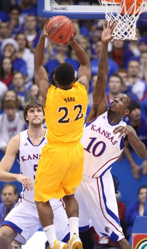 Kansas guard Tyshawn Taylor defends against a shot by Long Beach State guard Casper Ware during the first half on Tuesday, Dec. 6, 2011 at Allen Fieldhouse. In back is center Jeff Withey.