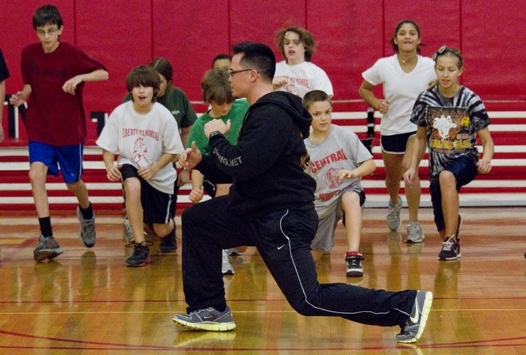 Chad Richards, center, demonstrates a stretch to the students at Liberty Memorial Central Middle School who are participating in the after-school Smart Strength program. The program, which was started by teacher Michel Loomis, aims to teach students how to eat right and be fit.