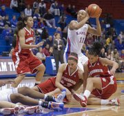 Out of a loose ball scramble, Aishah Sutherland (11) comes up with the ball and a shot at the basket during KU's home game against Big 10 team Wisconsin Thursday, Dec. 8, 2011.