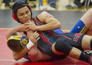 Lawrence High school wrestler Jhon Jacob, right, prepares to complete a pin of his Olathe South 113-pound weight class opponent Thursday, Dec. 8, 2011.