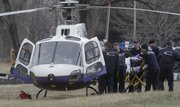 Emergency personnel put a man into a Lifestar helicopter near Lyon Park in North Lawrence, Friday afternoon. The man was injured in an accident while cutting branches from a tree.