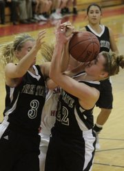 Free State's Abbey Casady (3) and Scout Wiebe (22) collide while fighting for an offensive rebound against Shawnee Heights on Friday, Dec. 9, 2011 in Topeka.