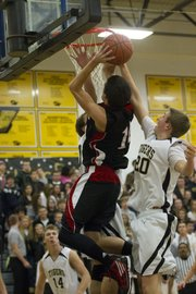 Lawrence High's KJ Pritchard fights through two Blue Valley defenders Friday, Dec. 9, 2011 in Stillwell.
