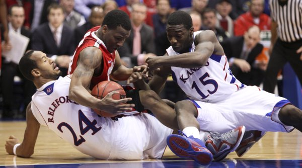 Kansas players Travis Releford and Elijah Johnson get tied up with Ohio State guard William Buford during the second half on Saturday, Dec. 10, 2011 at Allen Fieldhouse.