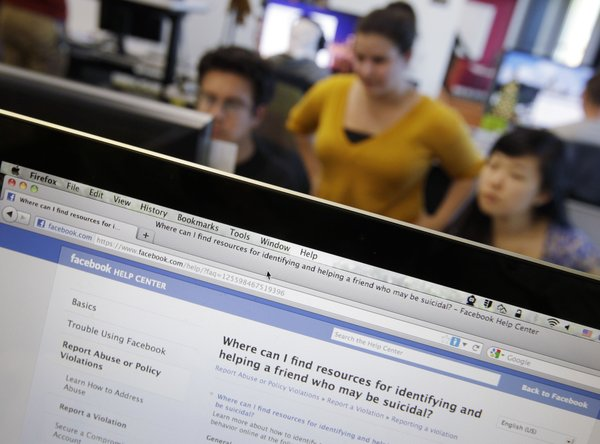 "Facebook's User Operations Safety Team workers look at reviews at Facebook headquarters in Menlo Park, Calif., Tuesday, Dec. 13, 2011. Facebook is making it easier for Facebook users who express suicidal thoughts to get help. A program launching on Tuesday enables Facebook users to instantly connect with a crisis counselor through Facebook's ""chat"" messaging system."