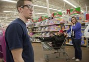 A Wal-Mart store employee, left, helps KU basketball player Naadir Tharpe, center in basket, and Kelli Blacklock, student manager, locate some items as members of the KU men's basketball team shopped for Christmas gifts for 15 families at the south Iowa Wal-Mart Thursday night, Dec. 15, 2011.