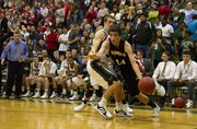 Lawrence High guard KJ Pritchard dribbles out of a Free State double team Friday, Dec. 16, 2011 at FSHS.